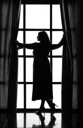 silhouette of a woman in a long peignoir near a large window in the morning