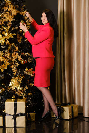 beautiful adult woman in red suit decorates christmas tree