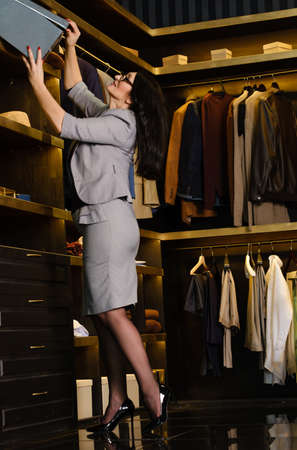 beautiful adult woman in a strict gray suit takes out a box from the shelf to the dressing room