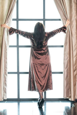 woman in a long peignoir near a large window in the morning