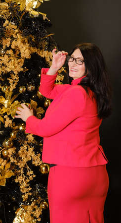 beautiful adult woman in stylish red suit decorates christmas tree