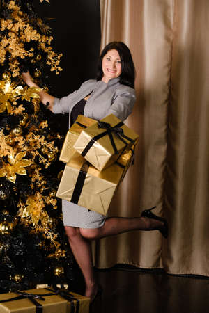 beautiful adult woman in stylish gray suit with gifts near christmas tree