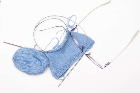 knitting needles and blue ball of thread on white background
