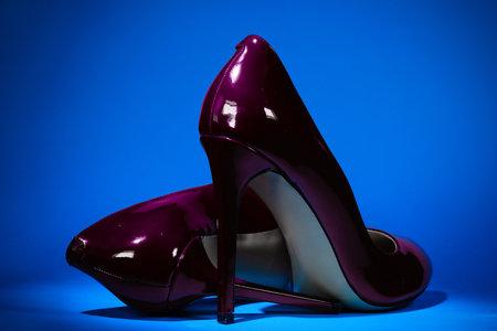 beautiful patent leather shiny female violet stilettos on a blue background