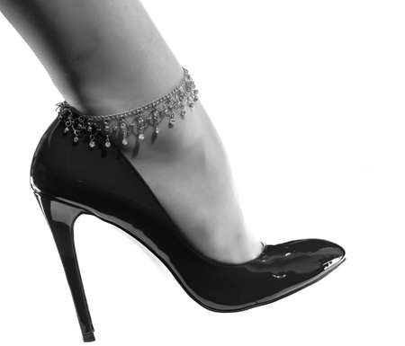 beautiful female leg with a decorative chain in a shiny black patent leather shoe on a whie