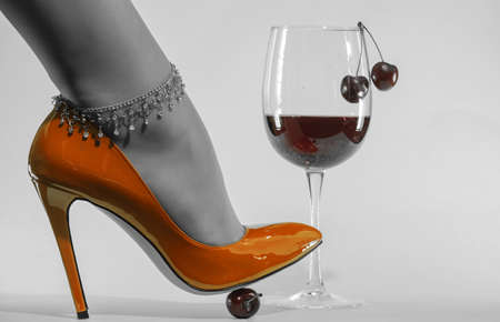 beautiful female legs with a decorative chain in shiny yellow patent leather shoes and a glass of wine