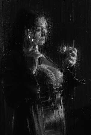 beautiful woman with a revolver in her hands and a glass behind a wet glass with raindrops