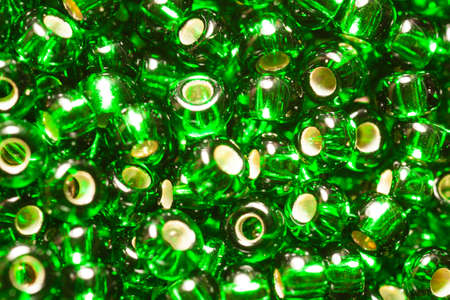 scattered green small beads in a heap