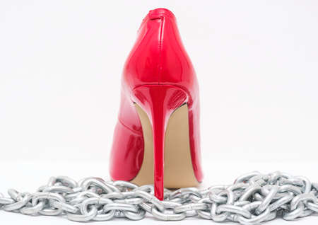 beautiful womens shiny patent red stiletto heels and steel chain on white background