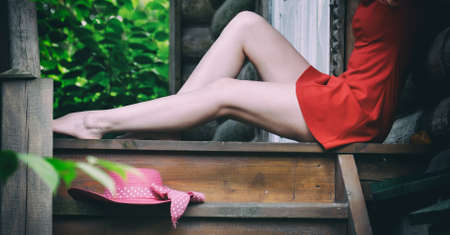 beautiful female legs on the old wooden porch Stock Photo