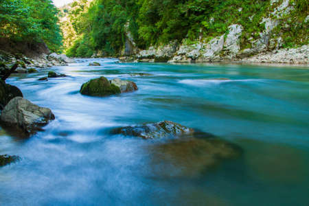 beautiful mountain river of turquoise color among stones and trees