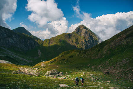 tourists in a beautiful mountain valley on a summer day Stock Photo