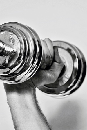 Silver dumbbell for motivation. Hand keep in fist dumbell. Stock fotó