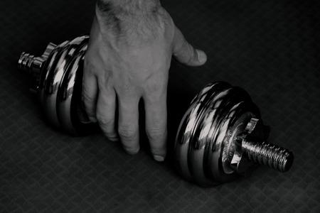 Fekete-fehér kép súlyzó kézzel