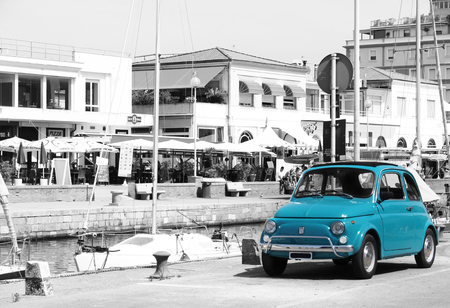 Parked Blue Fiat 500 in a beautiful port city.
