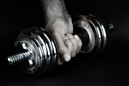 Hand holding a dumbbell in a fist. Dramatic proposal photo for sport.