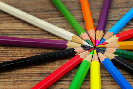 Circle of colored pencils on wooden texture. Preparing for school. Stock Photo