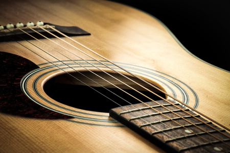 Close-up of acoustic guitar. Guitar in golden shades.