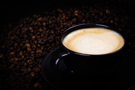 Black coffee cup with coffee beans. Hot drink for morning. Dark wallpaper with expresso.