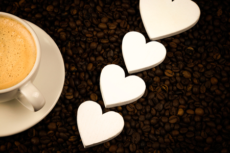 Espresso in white coffee with hearts and coffee beans. Background for coffee. Espresso wallpaper. Detail coffee with coffee beans.