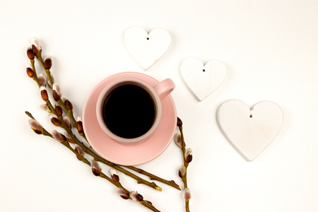 Spring coffe wallpaper with decoration. Hot drink on the white background. Pink coffe cup with flowers and hearts.