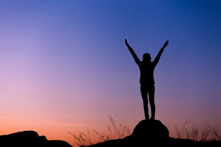 腕の美しいカラフルな空のに対して調達して幸せな若い女のシルエット。夏の夕日。風景