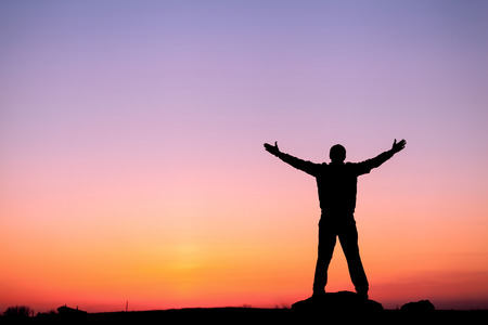 Silhouette of man with arms raised up and beautiful sky. Element of design. Summer sunset. Background