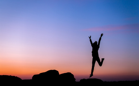Silhouette of happy young woman with arms raised up against beautiful colorful sky. Summer Sunset. Landscape 免版税图像