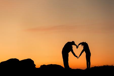 Conceptuele hart vorm, symbool van de mens. Vrouw en man hand silhouet over hemel bij zonsondergang op de achtergrond, metafoor voor liefde, valentijnsdag, romantisch, paar, huwelijk, romantiek, zomer of zonsopkomst Stockfoto