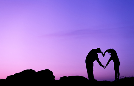 Conceptual heart shape, symbol of human. Woman and man hand silhouette over sky at sunset background, metaphor to love, valentine day, romantic, couple, wedding, romance, summer or sunrise