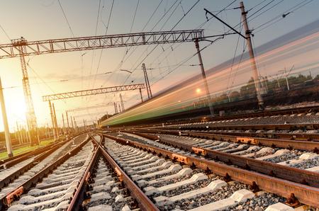 Trein hogesnelheidspassagiersvaartuigen op sporen met motion blur effect bij zonsondergang. Station in Oekraïne