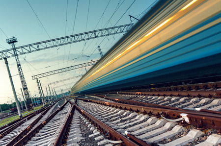 railroad transportation: High speed passenger train on tracks with motion blur effect at sunset. Railway station in Ukraine Stock Photo