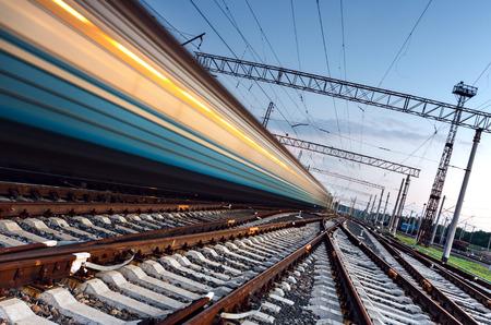 High-Speed-Personenzug auf Gleise mit Bewegungsunschärfe-Effekt bei Sonnenuntergang. Bahnhof in Ukraine