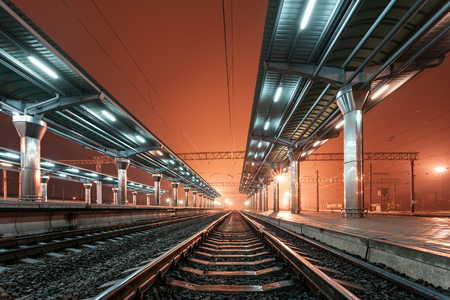 urban architecture: Railway station at night. Train platform in fog. Railroad in Donetsk.
