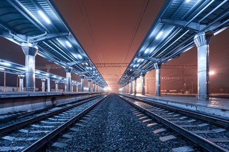 夜の鉄道駅。霧の駅のプラットフォーム。 写真素材