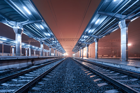 a line: Railway station at night. Train platform in fog.