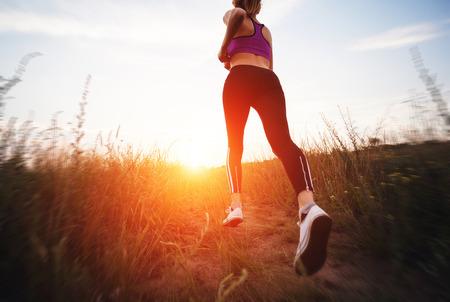 Jonge vrouw die op een landelijke weg bij zonsondergang in de zomer veld. Lifestyle sport achtergrond