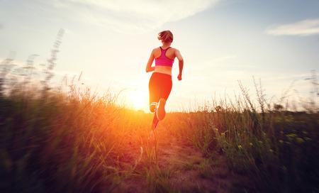corriendo: Mujer joven que se ejecuta en un camino rural al atardecer en el campo de verano. Fondo de estilo de vida deportiva