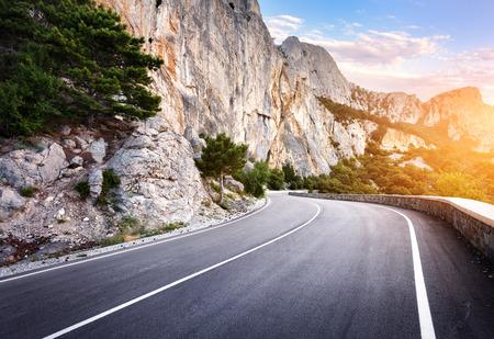 夕暮れの夏の森でアスファルトの道路。クリミア山脈。
