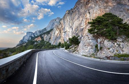 Asphalt road in summer forest at sunset. Crimean mountains.