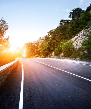 route: route d'asphalte dans la forêt de l'été au coucher du soleil. Montagnes de Crimée.