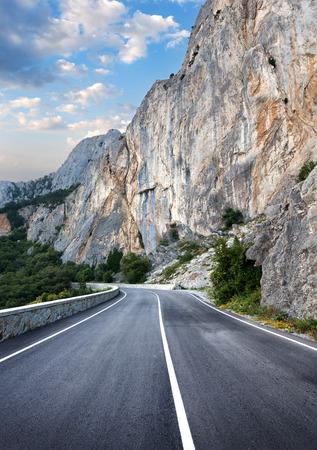 green road: Asphalt road in summer forest at sunset. Crimean mountains.