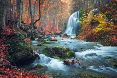 cascades: Beautiful waterfall in autumn forest in crimean mountains at sunset. Silver Stream Waterfall in Grand Canyon Of Crimea.