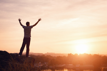 sunshine background: Silhouette of a man with raised-up arms at the beautiful sunset on the mountain. Background Stock Photo