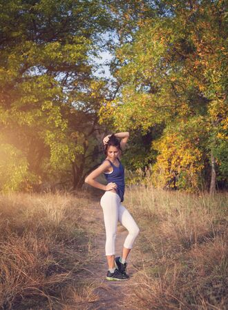healthy girl: Beautiful slim sporty woman standing at sunset in the field in autumn. Lifestyle background