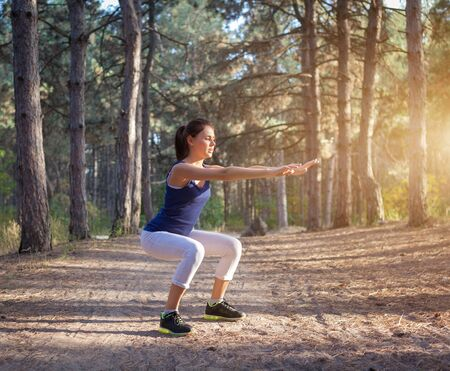 Young beautiful girl sports in the autumn forest at sunset