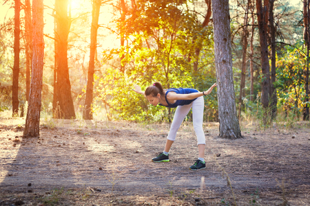 human arm: Young beautiful girl sports in the autumn forest at sunset