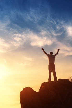 climbing: Silueta de un hombre con los brazos levantados en marcha en la hermosa puesta de sol en la montaña. Fondo