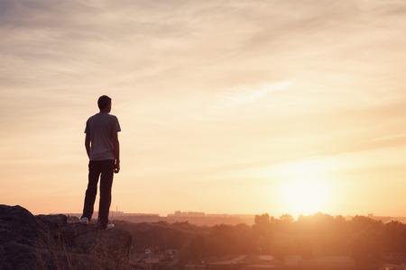 personas de espalda: Silueta de un hombre en la hermosa puesta de sol en la monta�a. Fondo