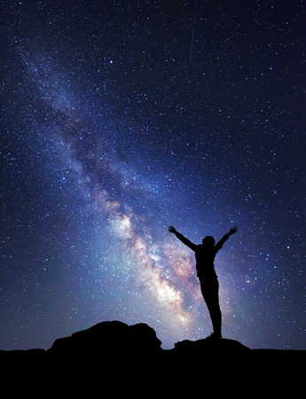starry: Milky Way. Night sky with stars and silhouette of a woman with raised-up arms. Stock Photo